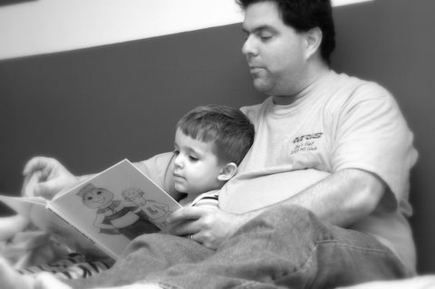 Black and white photo of a father reading to his son